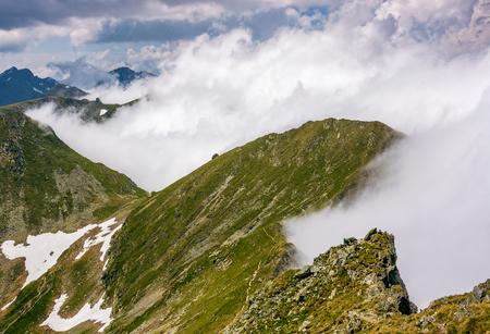 안개가 자욱한 날씨에 바위 언덕에 가파른 슬로프의 가장자리. 산의 극적인 풍경 스톡 콘텐츠