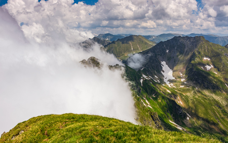 edge of steep slope on rocky hillside in foggy weather. dramatic scenery in mountains Reklamní fotografie