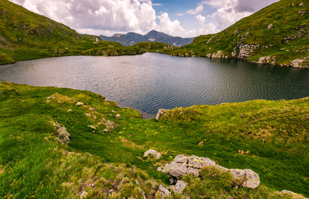 clear lake in mountains with grass on rocky hillside. beautiful mountain ridge in far distance. dramatic weather in picturesque summer scenery Stock Photo