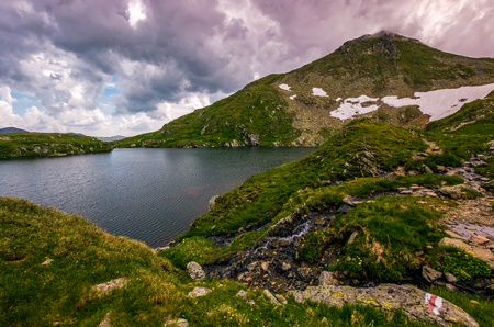 clear lake in mountains with snow and grass on rocky hillside. dramatic weather in picturesque summer scenery