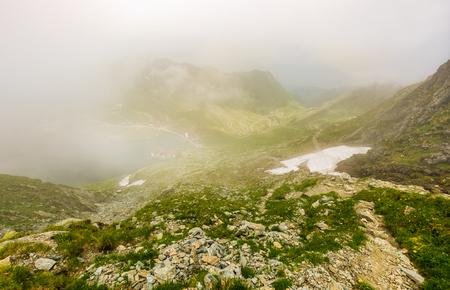 霧の balea 湖の上の岩が多い山腹の急斜面。ルーマニア語山の神秘的な天気 写真素材