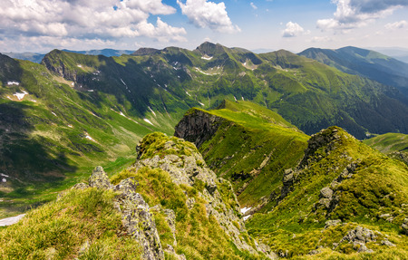 valley in romanian mountains view from the edge above. gorgeous summer landscape in fine weather with cloudy sky