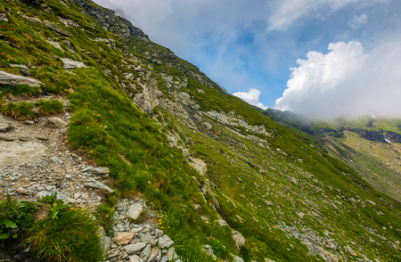 曇りの天候で岩が多い山腹の急斜面の端。山の劇的な風景
