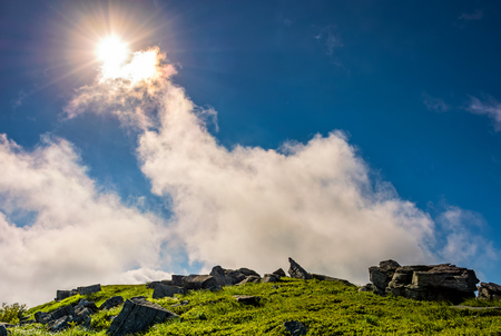 sunburst on a blue sky with clouds over the mountains with rocky hillside Stock Photo