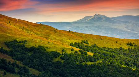 mountain ridge with peak behind the hillside. beautiful summer background at sunset with red sky;