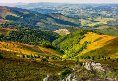 Landscape with grassy meadow and giant boulders on the edge of a slope in Carpathian mountain ridge.
