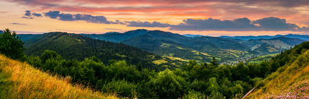 panorama of mountain ridge with peak behind the hillside. beautiful summer background at sunset with red sky Stock Photo