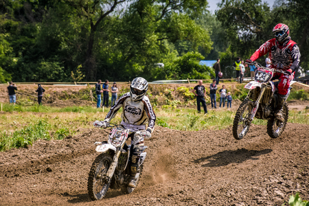 Uzhgorod, Ukraine - May 21, 2017: Extreme enduro MOTO SPORT. KTM racers turn on a corner in dirt. TransCarpathian regional Motocross Championship Editorial