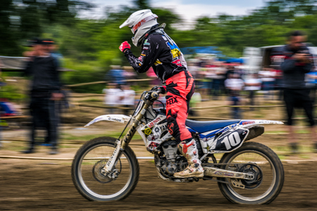 Uzhgorod, Ukraine - May 21, 2017: MX rider Finish the race. Motion blur with flying dirt. TransCarpathian regional Motocross Championship