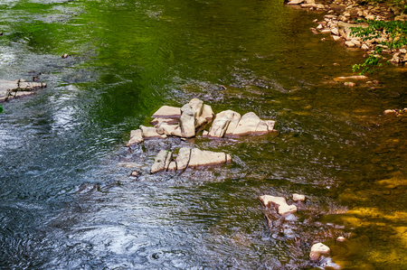 colorful surface of the forest river. natural background with stone and water textures