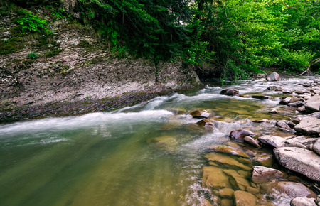 powerful green forest stream under the cliff. beautiful nature background Stock Photo