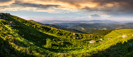 panorama of mountain ridge with peak behind the hillside. beautiful summer background at sunset with cloudy sky Stock Photo