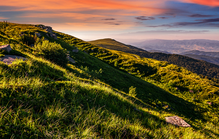 mountain ridge with peak behind the hillside. beautiful summer background at sunset with red sky Stock Photo
