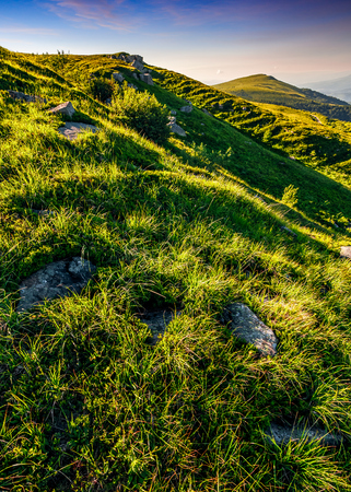 mountain ridge with peak behind the hillside. beautiful summer background at sunset with reddish sky Stock Photo