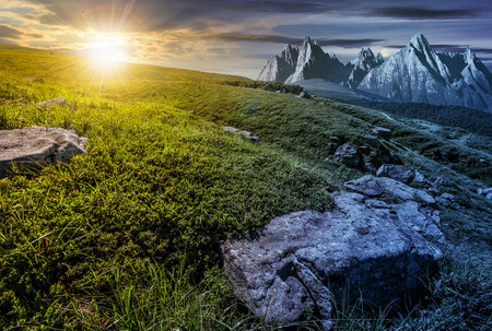 Day and night time change concept in High Tatra mountain summer landscape. Sun and moon over meadow with huge stones among the grass on top of the hillside near the peak of mountain range