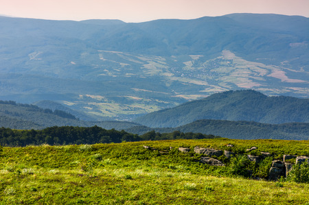 landscape with grassy meadow with giant boulders on the slope of a hill in Carpathian mountain ridge on a beautiful sunny summer day