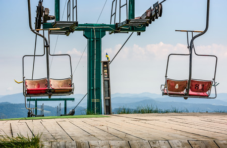 empty ski elevator with red chairs on top of a hill Gymba. Carpathian mountain ridge Borzhava, Ukraine. Lovely mountain landscape with clear sky Stock Photo