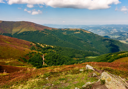 Carpathian Mountains with its peaks, hills, meadows and forests under the blue sky with clouds in late summer day Stock Photo