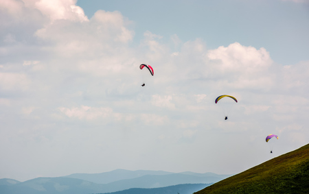 Skydivers fly over the mountains. Parachute extreme sport Stock Photo - 83278862