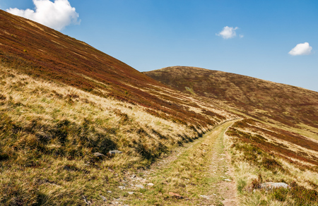 road through mountains with reddish hills. beautiful september weather Stock Photo