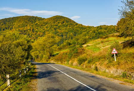 asphalt road with limitation sign in mountainous countryside. beautiful early autumn morning scenery Stock Photo