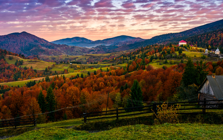 Exquisite late autumn sunrise in mountainous countryside. gorgeous purple sky over the village in valley with red foliage forest