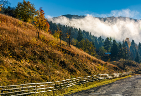 countryside road and fence at the mountain foot. cloud rising up from the forest at autumn morning Stock Photo