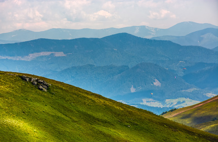 beautiful late summer landscape in carpathians. three skydivers fly over the valley Stock Photo - 83550564