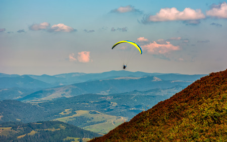 Skydiver flying in the clouds over the countryside valley at sunset. parachute extreme sport