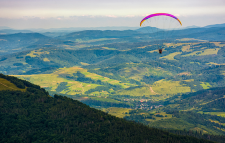 Skydiver flying in the clouds over the village in valley at sunset. parachute extreme sport Stock Photo - 83609135