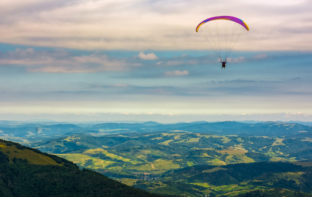 Skydiver flying in the clouds over the rural valley at sunset. parachute extreme sport Stock Photo - 83609136