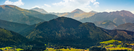 Panorama of High Tatras mountain ridge in Poland Countryside. Resort village Zakopane can be seen at the foot of the hill Stock Photo - 83609162