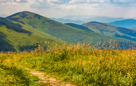 tourist stand in a grass on a meadow near dirt road observing mountain ridge. beautiful summer landscape in Carpathian mountains under cloudy sky