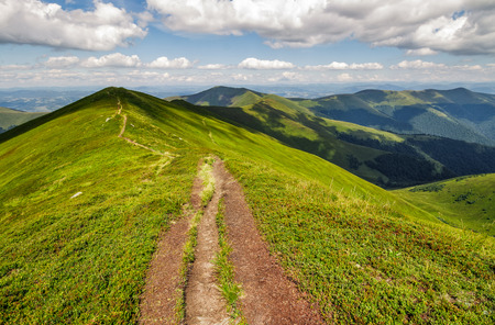 footpath on top of a mountain ridge with grassy slippery slopes. gorgeous scenery in wonderful summer weather with few clouds on a blue sky Stock Photo