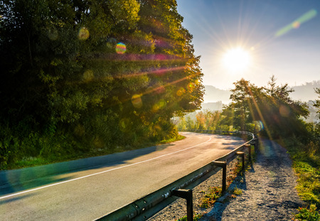 metal fence by countryside road through forest. beautiful bright weather in early autumn sunrise Stock Photo