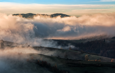 clouds and fog rising over countryside. rural fields on hills in gorgeous autumn sunrise