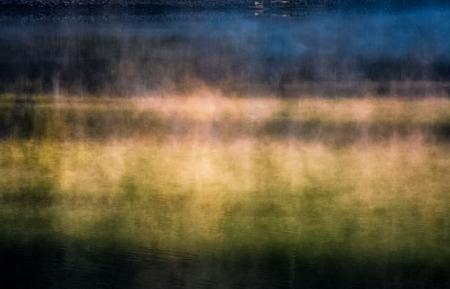 Close-up van mistig bosmeeroppervlak bij zonsopgang. Prachtige natuur achtergrond van kleurrijke rook stijgt over het water