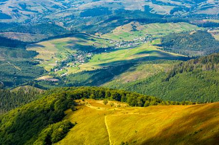 農村部の谷に丘の下のパス。村と山の麓の森の素敵な田舎の夏の風景