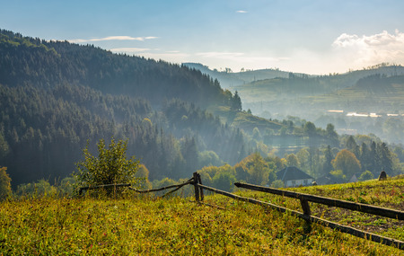 beautiful area in mountainous countryside. fence through hillside with rural fields near the forest in early autumn morning mist Stock Photo