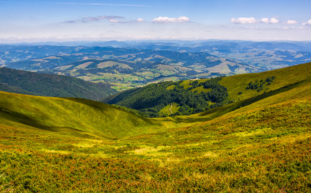 view to the rural valley in summer. beautiful scenery observation from the hillside on high mountain in fine weather inder blue sky with clouds