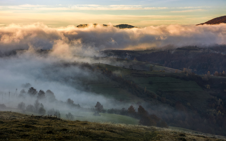 thick fog rising over the rural hills dawn. dramatic Carpathian countryside autumnal scenery