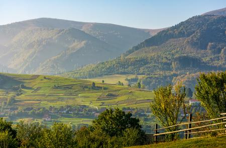 山間の田園地帯の美しい農村地帯。秋の早朝の霧で山の畑にフェンス