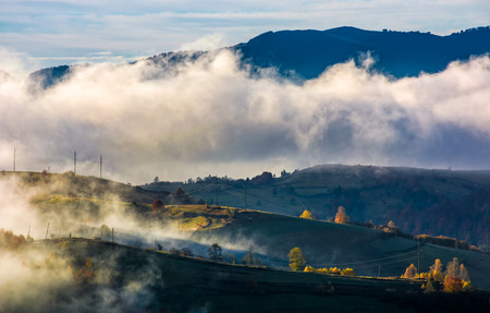 fog rising over the rural hills in morning light. dramatic Carpathian countryside autumnal scenery