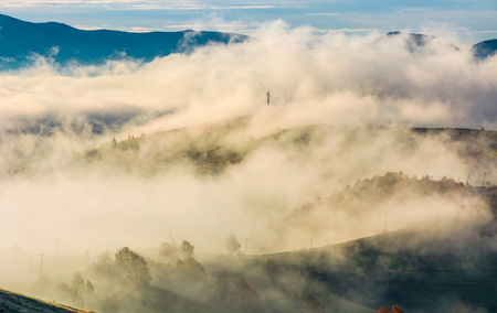 thick fog over the rural hills in morning light. dramatic Carpathian countryside autumnal scenery Stock fotó