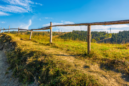 wooden fence along the path through countryside. grassy fields and forest mountainous Carpathian area