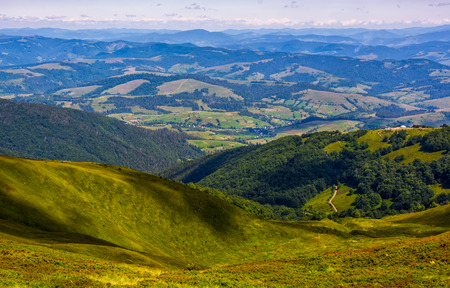 view to the rural valley in summer. beautiful scenery observation from the hillside on high mountain Stock Photo