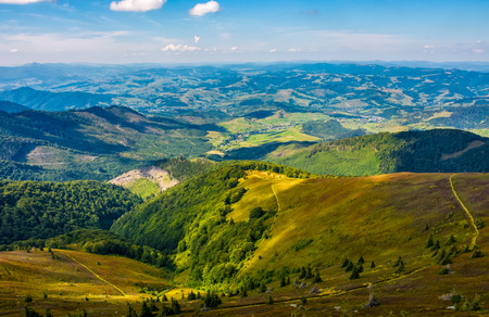 beautiful valley in countryside view from hillside. hilly landscape with meadow and forests under the blue evening sky with clouds Stock Photo