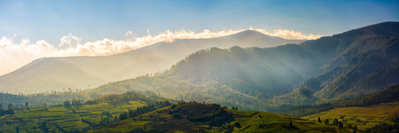 panorama of mountainous rural area at sunrise. Gorgeous autumnal morning weather with clouds above the mountains and fog in valley Stock Photo