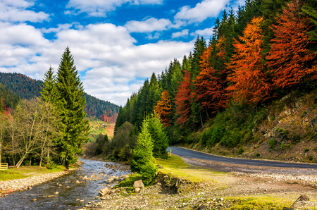 narrow forest river by the road in autumnal countryside. lovely nature scenery with colorful hills in a distance under cloudy sky Stock Photo
