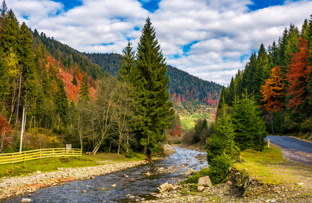 river in autumnal countryside with spruce forest. wooden fence of a tourist camping place in lovely nature scenery with colorful hills in a distance under cloudy sky
